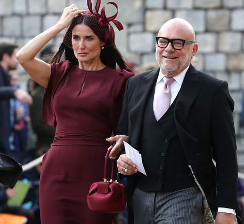 Actress Demi Moore hold onto her hat as she arrives at St George's Chapel.