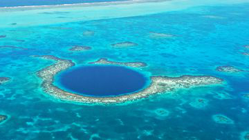 Situated in the centre of Lighthouse Reef off the coast of Belize, the Blue Hole is a giant marine sinkhole that is 318 m in diameter and 124m deep.