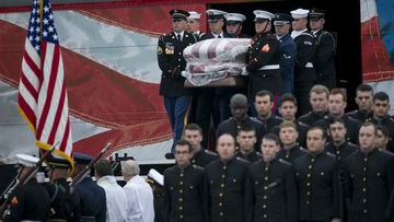 A joint military honor guard carries the casket of former President George H.W. Bush after it arrived by a presidential funeral train at Texas A&M University in College Station, Texas, for burial at the George Bush Presidential Library