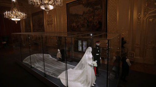 Members of staff from Windsor Castle stand next to the the wedding outfits of the Duke and Duchess of Sussex.
